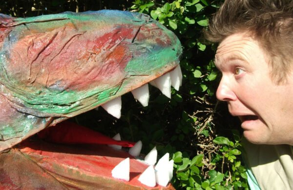 Actor looking worryingly into mouth of T-rex