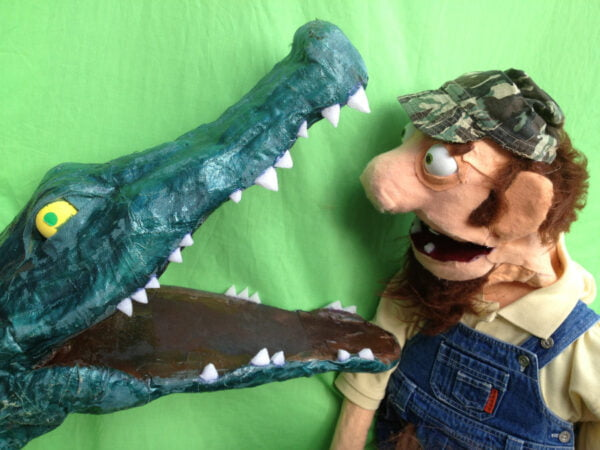 Puppet man looking down open mouth of a crocodile