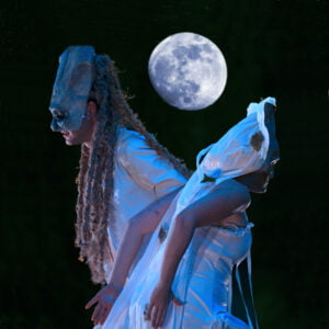 Two actors in costume underneath a full moon
