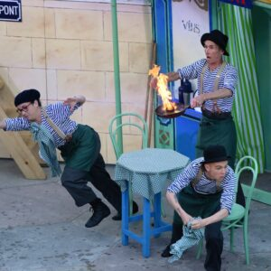 Three performers, on set, dressed in mime gear. One has a frying pan alight with flames as the other two are jumping out of the way.