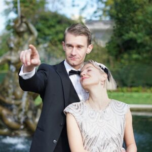 Man pointing into distance as lady leans into him