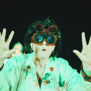 Mad scientist wearing goggles under a green light