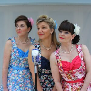 The Ritzy Belles posing around microphone