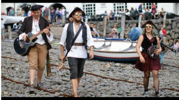 Three pirates walking on a pebbled beach