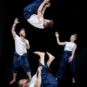 Four circus performers wearing white t-shirts and overalls, performing various acrobatic moves.