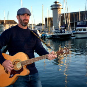 WIll Keating playing guitar in front of a harbour scene