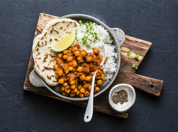 Vegetable curry with rice and naan in a bowl.